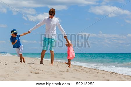 father with son and daughter play at beach, family at beach