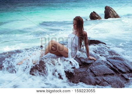 Sensual brunette woman in white dress with wet hair sitting on the rock over beautiful sea background