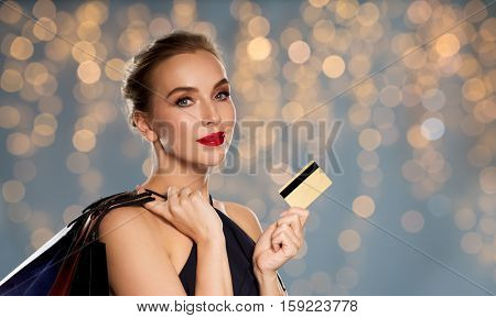 people, luxury and sale concept - beautiful woman with credit card and shopping bags over holidays lights background