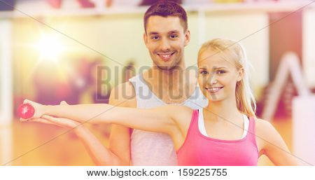 fitness, sport, training, gym and lifestyle concept - male trainer with woman working out with dumbbell