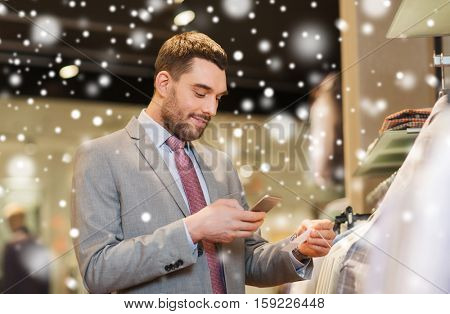 sale, shopping, fashion, technology and people concept - happy man in suit with smartphone choosing clothes at clothing store over snow
