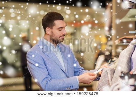 sale, shopping, fashion, style and people concept - elegant young man in jacket choosing clothes and looking at price tag in mall or clothing store over snow