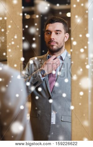 sale, shopping, fashion, style and people concept - young man choosing and trying jacket on and looking to mirror in mall or clothing store over snow