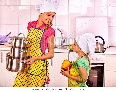 Two sisters in caps chefs cook in the kitchen. Happy children holding pots and vegetables.