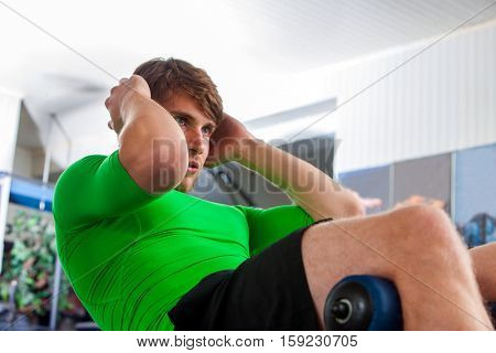 Man working his abdominal crunches on bench in gym. Crunches with its own weight.