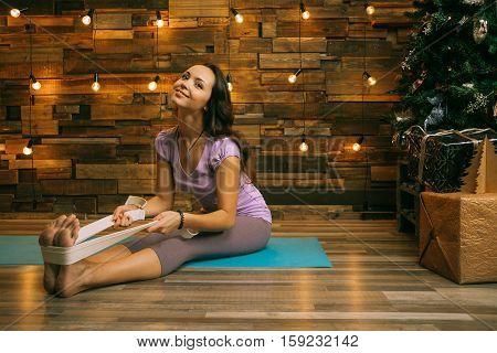 Christmas Yoga. Yong Woman Doing Yoga Near Fir-tree