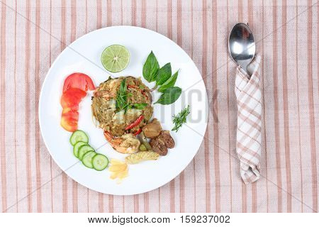 Thai food Fried jasmine rice in green curry with meat (shrimp ,squid ,chicken liver and chicken hearts) topped halve green lemon ,sliced tomato ,cucumber ,correspondents and basil leaf.