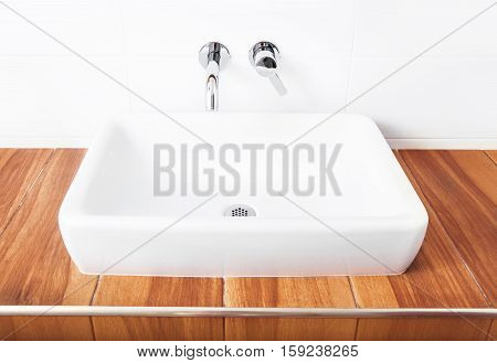 White porcelain washbasin and chrome-plated faucets in the bathroom.