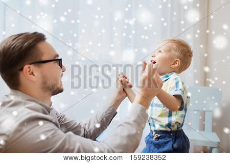 family, childhood, fatherhood, leisure and people concept - happy father and little son playing and having fun at home over snow