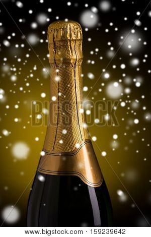 drink, alcohol, christmas, new year and winter holidays concep - close up of bottle of champagne with blank golden label over dark background and snow