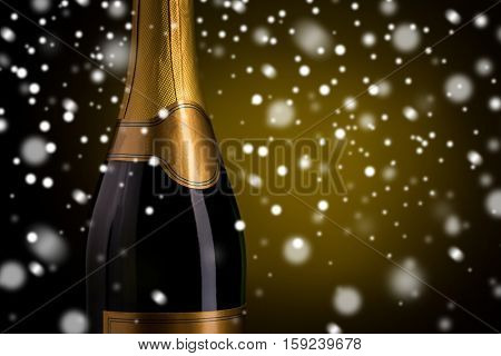 drink, alcohol, christmas, new year and winter holidays concept - close up of bottle of champagne with blank golden label over dark background and snow