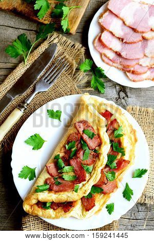 Fried bacon omelette. Omelette stuffed with bacon and parsley on a plate, bacon slices on a plate, fork, knife, cutting board, parsley sprigs on wooden background. Homemade eggs breakfast. Top view