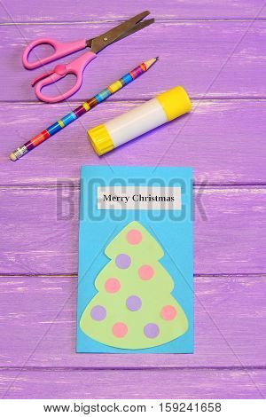 Greeting card Merry Christmas. Cute greeting card with paper Christmas tree, scissors, glue stick, pencil, on lilac wooden background. Handmade Christmas crafts ideas for children. Closeup. Top view