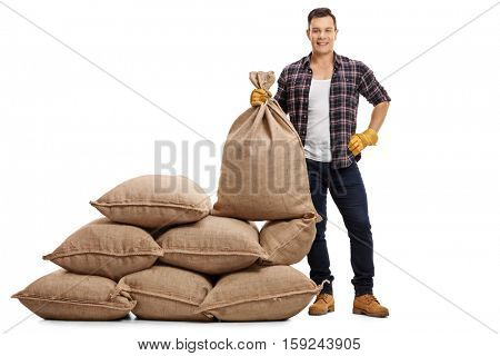 Full length portrait of a young farmer standing next to a pile of sacks and holding a burlap sack isolated on white background