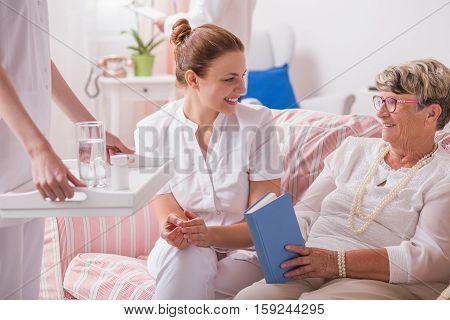 Caregiver With Medicines For Elderly Patient