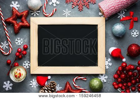 Christmas Xmas New Year holiday background with empty black chalkboard for your text and various festive decorations santa hat bauble snowflake star bow ball pinecone berry candy cane top view