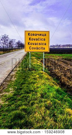 Yellow Road Sign under the Cloudy Sky in several languages
