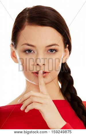 Young woman with finger on lips