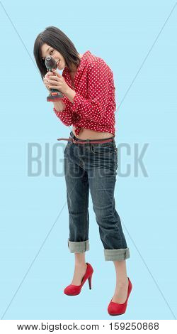 pretty young woman holding cordless drill on blue background