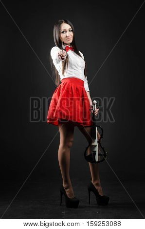 A smiling girl standing with a violin on a black background fiddlestick is directs at the camera