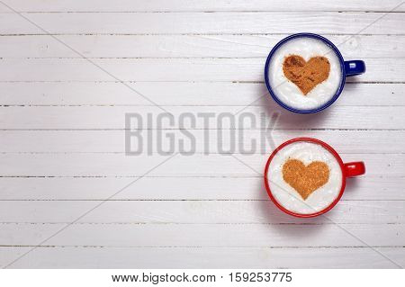 Two cups of coffee with heart shape symbol on wooden white background
