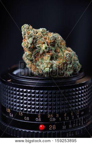 Dried cannabis bud in top of digital camera lens - marijuana photography concept