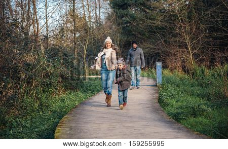 Happy kid and woman holding hands and running over a wooden pathway while man looking in the background