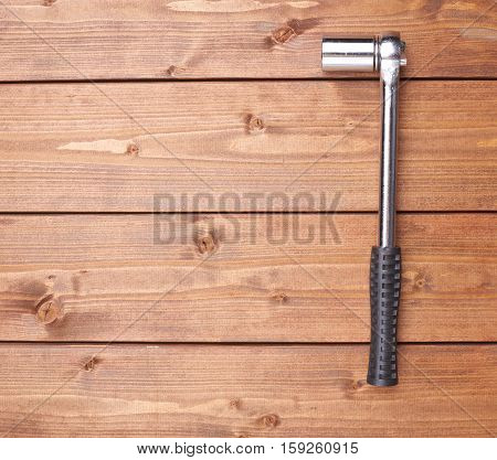 Socket metal wrench with black handle on wooden brown surface