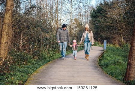 Family holding hands while walking over a wooden pathway into the forest