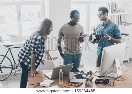 Sharing opinions. Group of young business people working and communicating together while standing in creative office