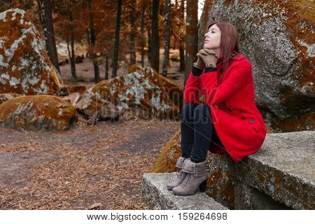 Young woman feeling depressed sitting on a stone table and bench on a forest wearing a red overcoat during winter