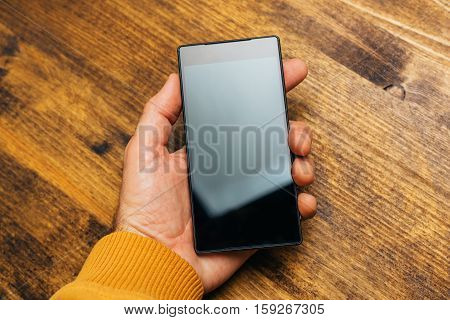 Top view of male hand holding smart phone with blank screen on desk