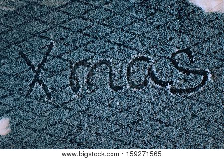 write x-mas in the snow, the snow on iron background, inscription,