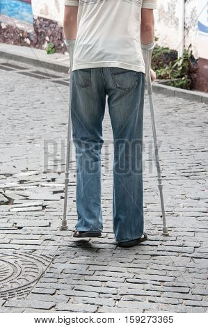 The Disabled Person Walks In Park On Crutches