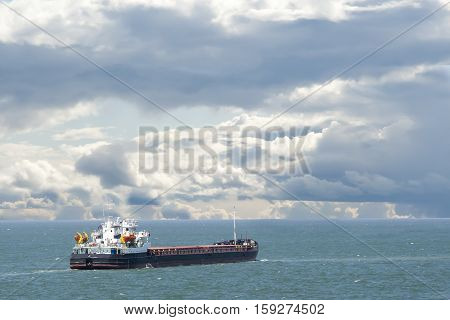 cargo ship sails on the sea in summer cloudy day
