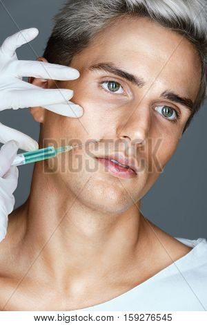 Doctor giving injection on face of young man. Photo of Man getting injection in the nasolabial folds. Cosmetology concept