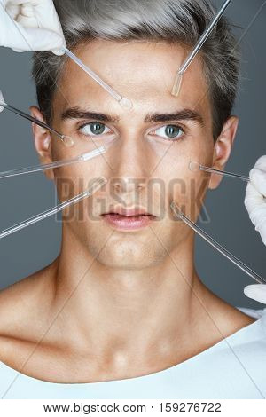 Young man and beautician hands with glass cream sticks. Attractive man receiving the skin treatment procedures. Beauty Face