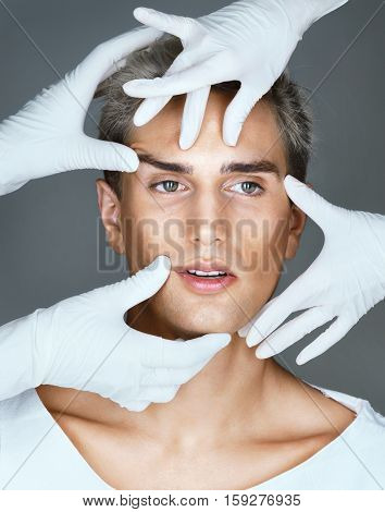 Hands of doctors in gloves touching face of beautiful young man. Cosmetology concept