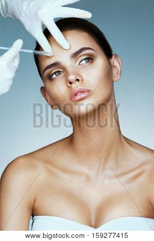 Attractive woman making injection in forehead. Doctor makes cosmetic injection. Beauty Treatment.