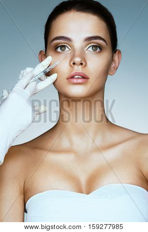 Beautiful young woman gets beauty injection in eye area from beautician. Portrait of young woman getting cosmetic injection. Clean Beauty concept