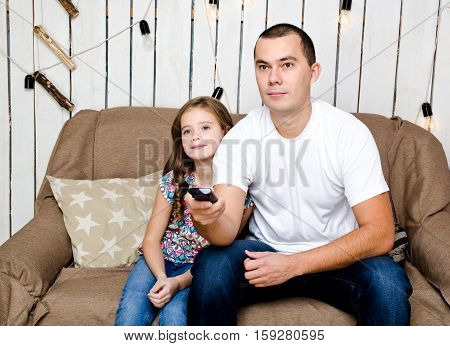 Cute little girl and her father watching tv yong man holding a remote control