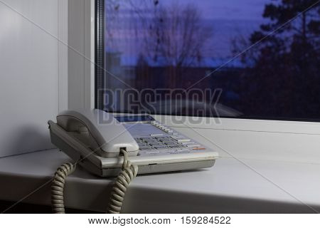 White old-fashioned phone, located on a windowsill.
