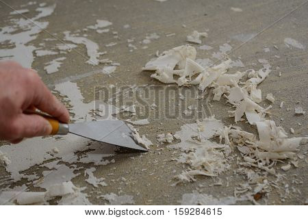 Handyman removes glue from the floor with a special spatula - close-up