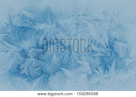 Blue frost pattern on a window glass in the winter (as an abstract winter background in subdued colors) retro style