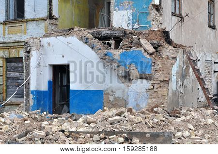 Process of demolition of a residential building. Ruined walls bricks in the foreground. Theme of war refugees destruction and reconstruction.