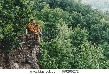 Traveler young man resting on top of cliff and drinking tea from thermos outdoor