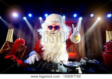 Dj Santa Claus mixing at the party Christmas, raised his hand up