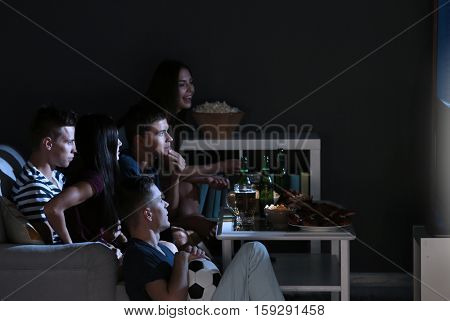 Young fans watching football match on TV late in evening with beer and snacks