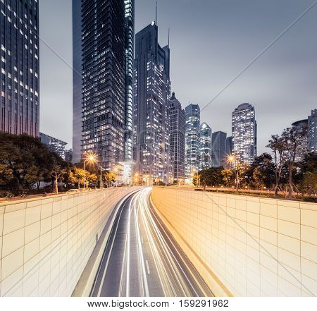 light trails on tunnel entrance with modern buildings in shanghai at night