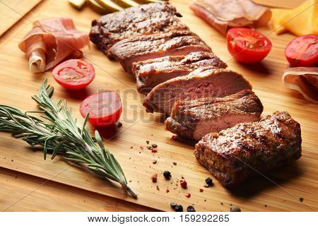 Grilled steak and appetizers on cutting board